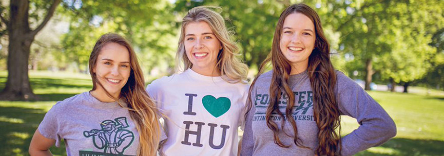 Three girls are standing in the grass at Huntington University wearing HU t-shirts.